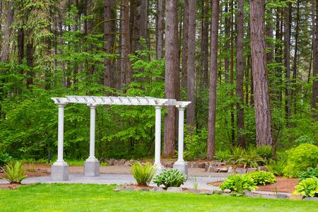 venue: Outdoor wedding ceremony venue with white pergola set against some Oregon trees.