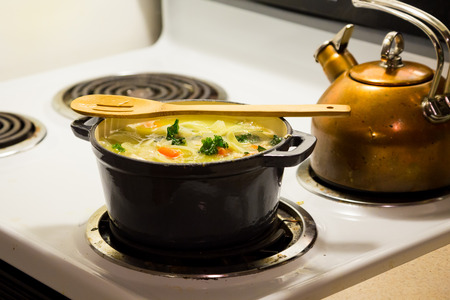 Dutch oven on a stove while cooking chicken noodle soup.