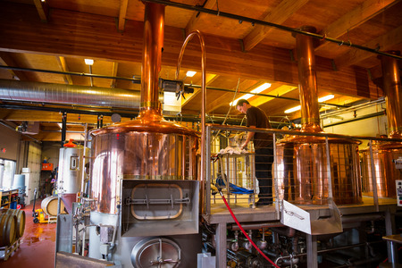 fermenters: Bend, OR, USA - January 12, 2014: Beer making inside of the Crux Fermentation Project with large fermenters and industrial equipment.