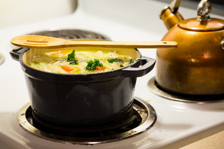 dutch: Dutch oven on a stove while cooking chicken noodle soup.