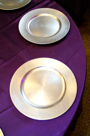 Silver plates ready for food at a restaurant wedding reception.