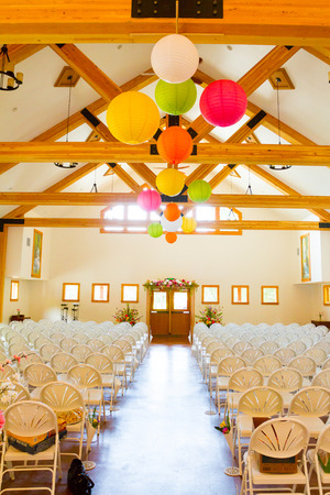 venue: Indoor wedding venue location for a ceremony with rows of white chairs. Editorial