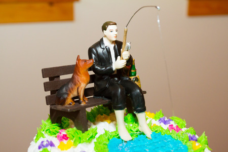topper: Cake topper at a wedding reception with the groom fishing and his dog next to him.