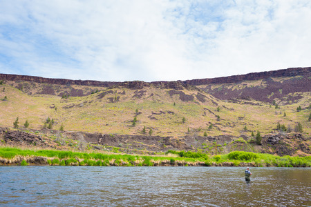 Experienced fly fisherman fishing the Deschutes River in Oregon, casting for fish while standing in the water. 版權商用圖片