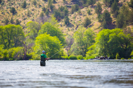 Experienced fly fisherman fishing the Deschutes River in Oregon, casting for fish while standing in the water. Фото со стока - 28666617
