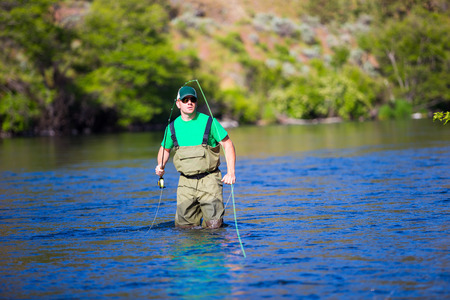 Experienced fly fisherman fishing the Deschutes River in Oregon, casting for fish while standing in the water. Фото со стока - 29264880