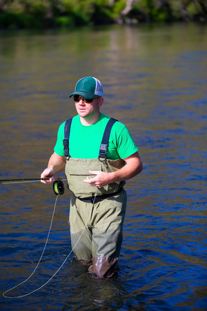 Experienced fly fisherman fishing the Deschutes River in Oregon, casting for fish while standing in the water. Фото со стока - 29264890