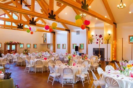 Tafels en stoelen op een bruiloft receptie op een indoor locatie.