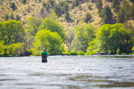 Experienced fly fisherman fishing the Deschutes River in Oregon, casting for fish while standing in the water. Фото со стока - 28767948