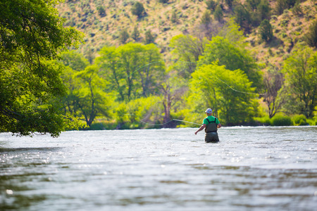 Experienced fly fisherman fishing the Deschutes River in Oregon, casting for fish while standing in the water. Фото со стока
