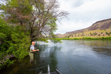 Experienced fly fisherman fishing the Deschutes River in Oregon, casting for fish while standing in the water. photo