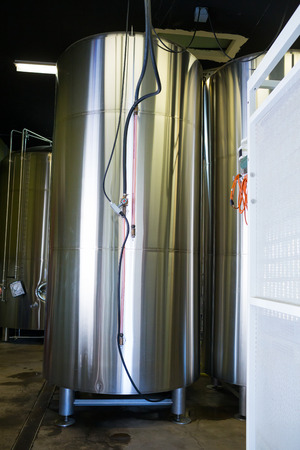 fermenters: Eugene, OR, USA - July 17, 2014: Stainless steel fermenters in the brewing room at Oakshire Brewery, a small craft beer maker in the Northwest. Editorial