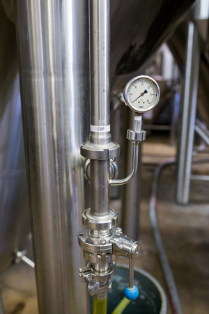 brewery: Eugene, OR, USA - July 17, 2014: Valves on a stainless steel fermenter in the brewing room of Oakshire Brewery.