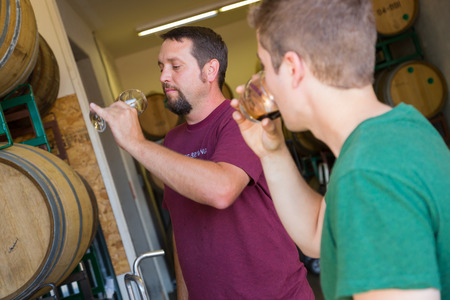Eugene, OR, USA - July 17, 2014: Master brewer and employee sampling and tasting limited edition bourbon barrel aged beers at Oakshire Brewing. Stok Fotoğraf - 32910230
