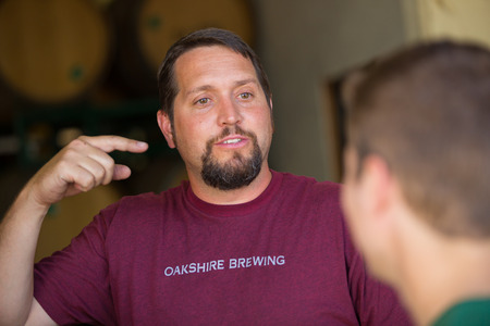 brewery: Eugene, OR, USA - July 17, 2014: Master brewer and employee sampling and tasting limited edition bourbon barrel aged beers at Oakshire Brewing.