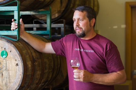 brewery: Eugene, OR, USA - July 17, 2014: Master brewer at Oakshire Brewing sampling and tasting bourbon barrel aged beers at the brewery. Editorial