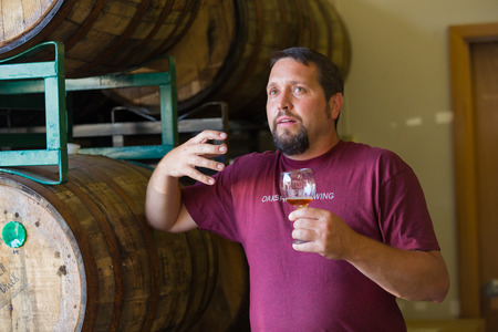 Eugene, OR, USA - July 17, 2014: Master brewer at Oakshire Brewing sampling and tasting bourbon barrel aged beers at the brewery. Stok Fotoğraf - 32910241