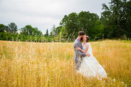 man woman kissing: Bride and groom kissing in a field on their wedding day.