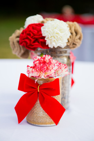 decor: Decorations and decor of red and white wedding flowers at a reception event.