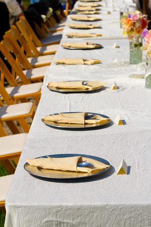 Dining table at a wedding reception outdoors with plates and silverware ready for eating.