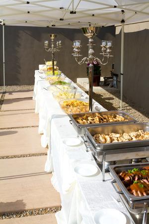 야외 텐트 아래 결혼식 뷔페에서 음식을받습니다.