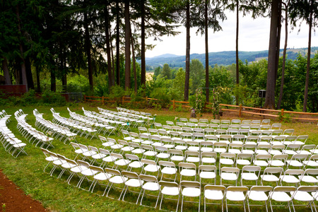 venue: Wedding ceremony at an outdoor venue with grass, trees, and white chairs.