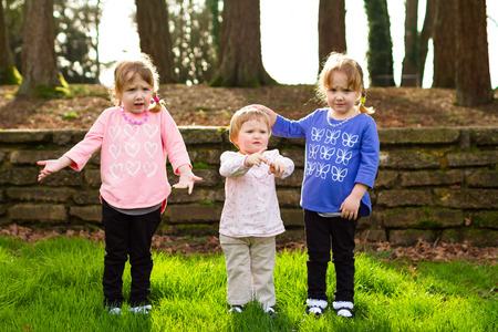 three sisters: Three sisters together at a park having fun together in natural light. Stock Photo
