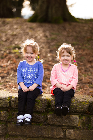 Lifestyle portrait of identical twin sisters at a park interacting and having fun together.