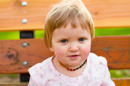 one year: Portrait of a one year old girl at a park with natural light. Stock Photo