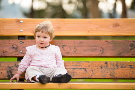 one year old: Portrait of a one year old girl at a park with natural light. Stock Photo