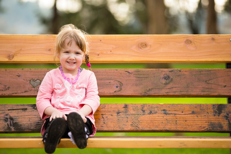 one person only: Lifestyle portrait of a young girl at a park with natural light. Stock Photo
