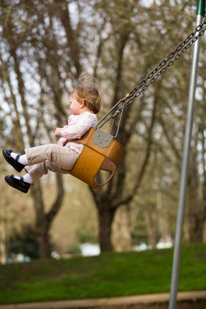 swing set: One year old girl on a swing set at a park in natural light. Stock Photo