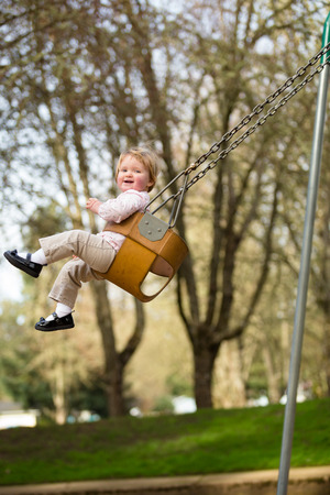 one year old: One year old girl on a swing set at a park in natural light. Stock Photo