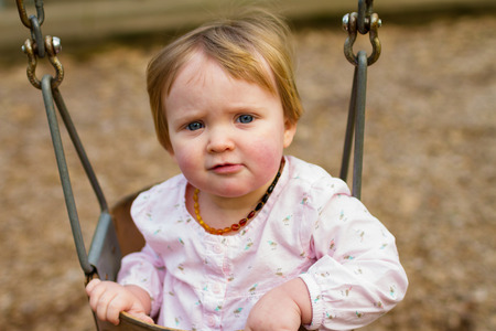 one year: One year old girl on a swing set at a park in natural light. Stock Photo