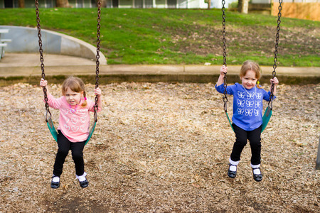 swing set: Identical twin girls at a park on a swing set in natural light.