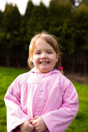 公園の雨コートで若い女の子の肖像画。この lifetsyle の写真は、自然光で撮影されました。 写真素材