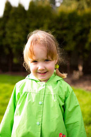 one person only: Portrait of a young girl at a park with a rain coat on. This lifetsyle photo was shot with natural light.