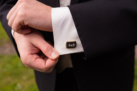 cuff links: Wedding attire detail of a groom on his wedding day before the ceremony. Stock Photo