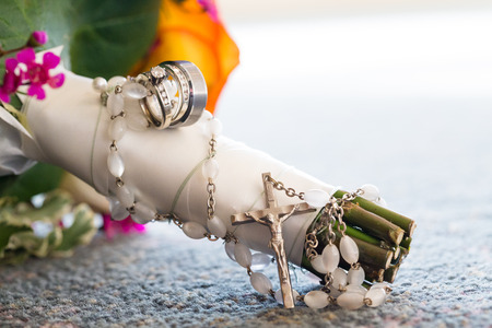 Rosary hangs from the bouquet of a bride on her wedding day with beautiful flowers and jewelry. Stock Photo