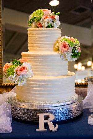 tiered: Wedding cake at a reception is a traditional tiered dessert cake. Stock Photo