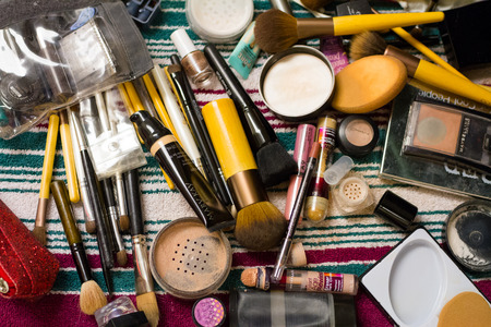 cosmetologies: Eugene, OR, USA - March 21, 2015: Makeup brushes and various makeup items on a table during wedding preparation.