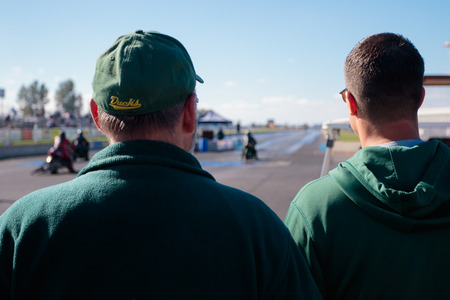 dragstrip: WOODBURN, OR - SEPTEMBER 27, 2015: Spectators watching motorcycle races from behind the starting line at the NHRA 30th Annual Fall Classic at the Woodburn Dragstrip.