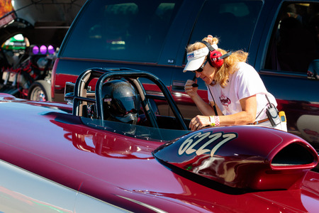 dragster: WOODBURN, OR - SEPTEMBER 27, 2015: Dragster driver and pit crew chief going over last minute adjustments before a race at the NHRA 30th Annual Fall Classic at the Woodburn Dragstrip.