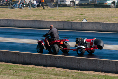 dragstrip: WOODBURN, OR - SEPTEMBER 27, 2015: Track worker drives an ATV with a drying machine on the back to dry the race surface at the NHRA 30th Annual Fall Classic at the Woodburn Dragstrip. Editorial