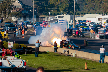 dragstrip: WOODBURN, OR - SEPTEMBER 27, 2015: Darin Bays Warped Speed Black Rat jet dragster blows fire and smoke towards spectators during the NHRA 30th Annual Fall Classic at the Woodburn Dragstrip.