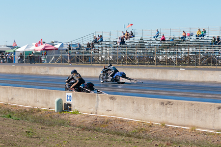 dragstrip: WOODBURN, OR - SEPTEMBER 27, 2015: Two motorcycles race down the track at the NHRA 30th Annual Fall Classic at the Woodburn Dragstrip.