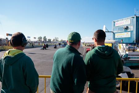 WOODBURN, OF - 27 SEPTEMBER 2015: Toeschouwers kijken naar motorraces van achter de startlijn bij de NHRA 30e jaarlijkse herfstschrijver uit de Woodburn Dragstrip. Redactioneel