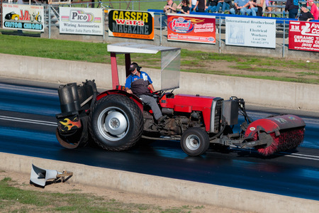 dragstrip: WOODBURN, OR - SEPTEMBER 27, 2015: Worker on a tractor cleans up the race surface after a crash at the NHRA 30th Annual Fall Classic at the Woodburn Dragstrip. Editorial