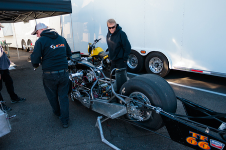 WOODBURN, OR - SEPTEMBER 27, 2015: Motorcycle mechanic and driver working on their team vehicle at the NHRA 30th Annual Fall Classic at the Woodburn Dragstrip.