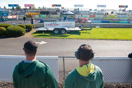 WOODBURN, OR - 27 september 2015: Twee toeschouwers kijken naar de startlijn aan de NHRA 30e jaarlijkse Fall Classic op de Woodburn Dragstrip. Redactioneel